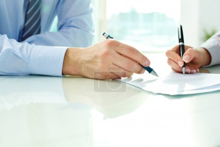Photo for Two business partners signing a document - Royalty Free Image