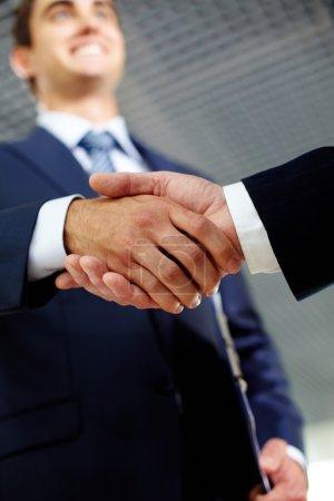 Photo pour Deux homme d'affaires secouant joyeusement les mains indiquant des négociations fructueuses - image libre de droit