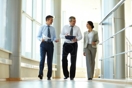 Photo for Confident business partners walking down in office building and discussing work - Royalty Free Image