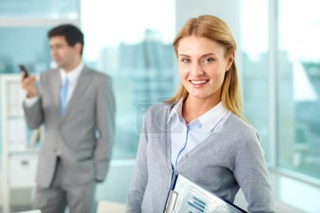 Photo for Smiling businesswoman looking at camera with busy man on background - Royalty Free Image