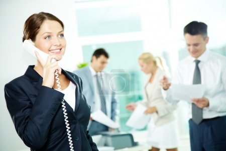 Photo for A beautiful businesswoman calling by the phone in working environment - Royalty Free Image