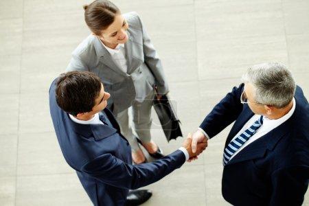 Photo pour Image de partenaires d'affaires poignée de main après avoir conclu un accord frappant avec une femme intelligente à proximité - image libre de droit