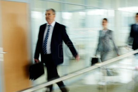 Photo for Businessman going along corridor with walking on background - Royalty Free Image