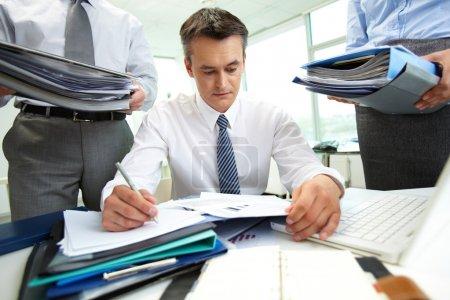 Photo pour Comptable confiant faisant des rapports financiers étant entouré de partenaires commerciaux avec d'énormes piles de documents - image libre de droit