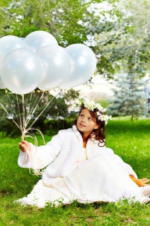Foto de Retrato de novia niña con globos sentado en el parque - Imagen libre de derechos