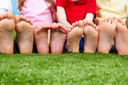 Photo pour Heureux amis assis sur l'herbe pieds nus - image libre de droit