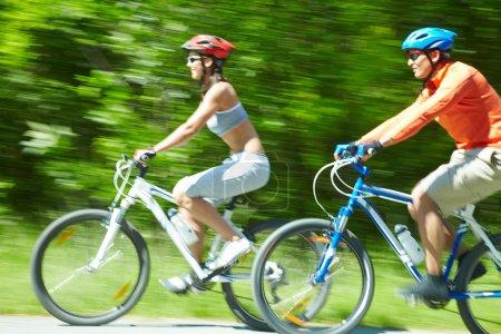Photo pour Image en mouvement de deux cyclistes circulant sur une route de campagne - image libre de droit