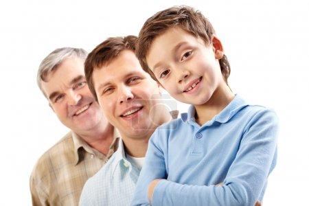 Foto de Tres miembros masculinos de la familia presentando tres generaciones sonriendo a la cámara - Imagen libre de derechos