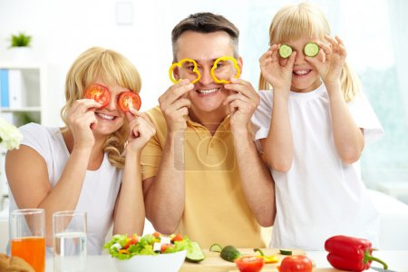 Photo for Cheerful family playing with vegetables in kitchen, healthy food - Royalty Free Image