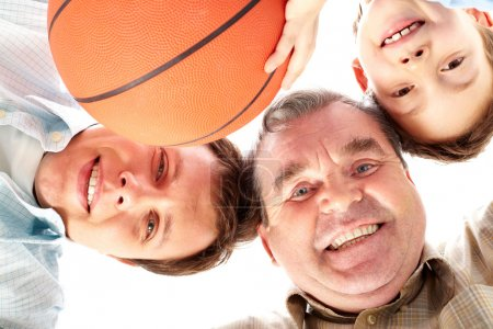 Photo for Below view of a father, grandfather and son looking at camera - Royalty Free Image
