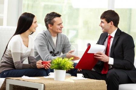 Foto de Retrato de pareja moderna escuchando Gerente explicación sobre las condiciones de la hipoteca - Imagen libre de derechos