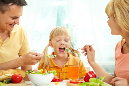 Photo for Portrait of happy parents feeding their daughter with salad in the kitchen - Royalty Free Image