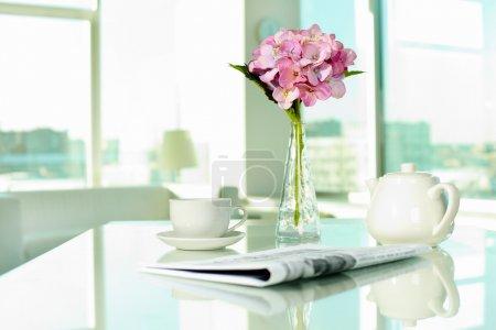 Photo pour Lieu de travail avec tasse en porcelaine et pot, Journal et bouquet de fleurs - image libre de droit