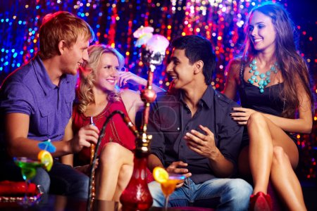 Photo for Happy friends drinking cocktails and smoking kalian in the nightclub - Royalty Free Image