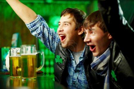 Foto de Felices hombres gritando mientras viendo fútbol coincida con la difusión en bar - Imagen libre de derechos