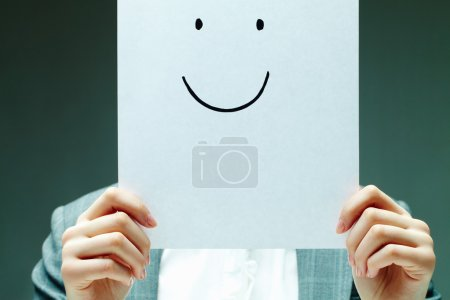 Photo for Image of female holding paper with drawn smile by her face - Royalty Free Image