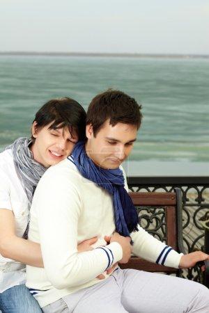Photo pour Jeune homme gay étreindre son amante souriant rêveusement - image libre de droit