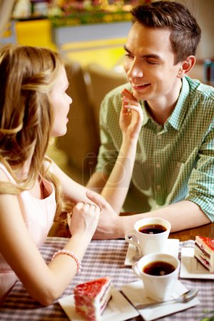 Photo for A young happy woman looking at her boyfriend and touching his face - Royalty Free Image
