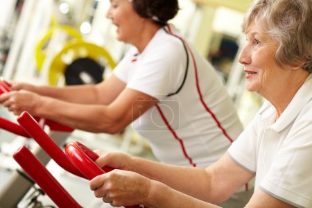 Photo for Tilt up of two active senior women doing fitness at gym - Royalty Free Image