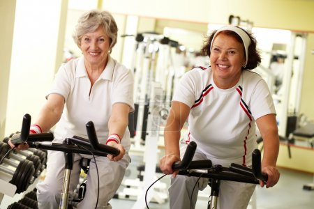 Photo for Portrait of two senior women on simulators in fitness club - Royalty Free Image