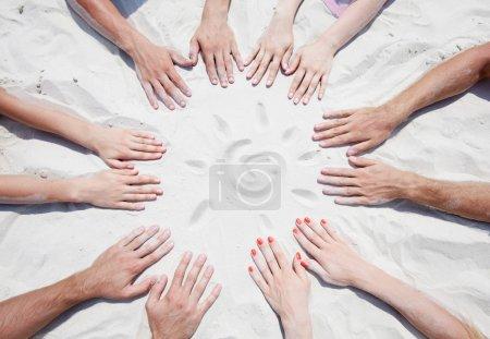 Photo pour Cercle des mains sur le sable avec un soleil - image libre de droit