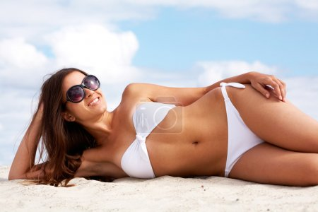Photo for Image of female in white bikini sunbathing on sandy beach - Royalty Free Image