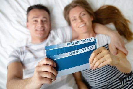 Photo pour Heureux jeune couple couché sur le lit avec des billets d'avion dans les mains - image libre de droit