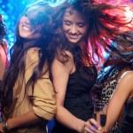 Young women having fun dancing at nightclub...