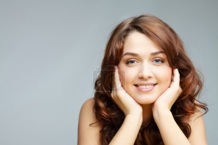 Photo for Portrait of charming girl looking at camera on grey background - Royalty Free Image