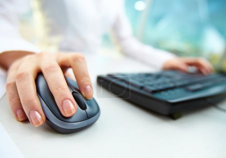 Photo for Image of female hands pushing keys of a computer mouse and keyboard - Royalty Free Image